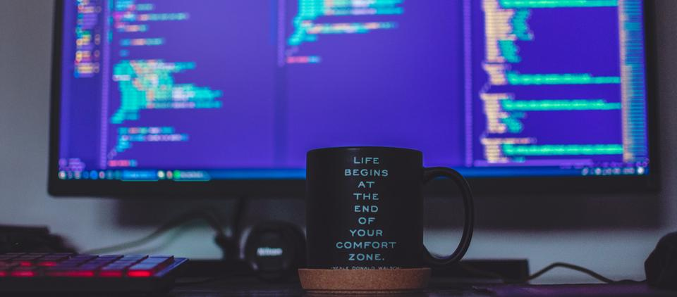 Picture of a remote working environment with a monitor with code and a mug that says 'Life begins at the end of your comfort zone'
